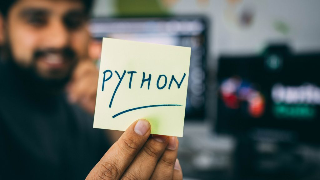 a data science intern holding a sticky note with Python written on it