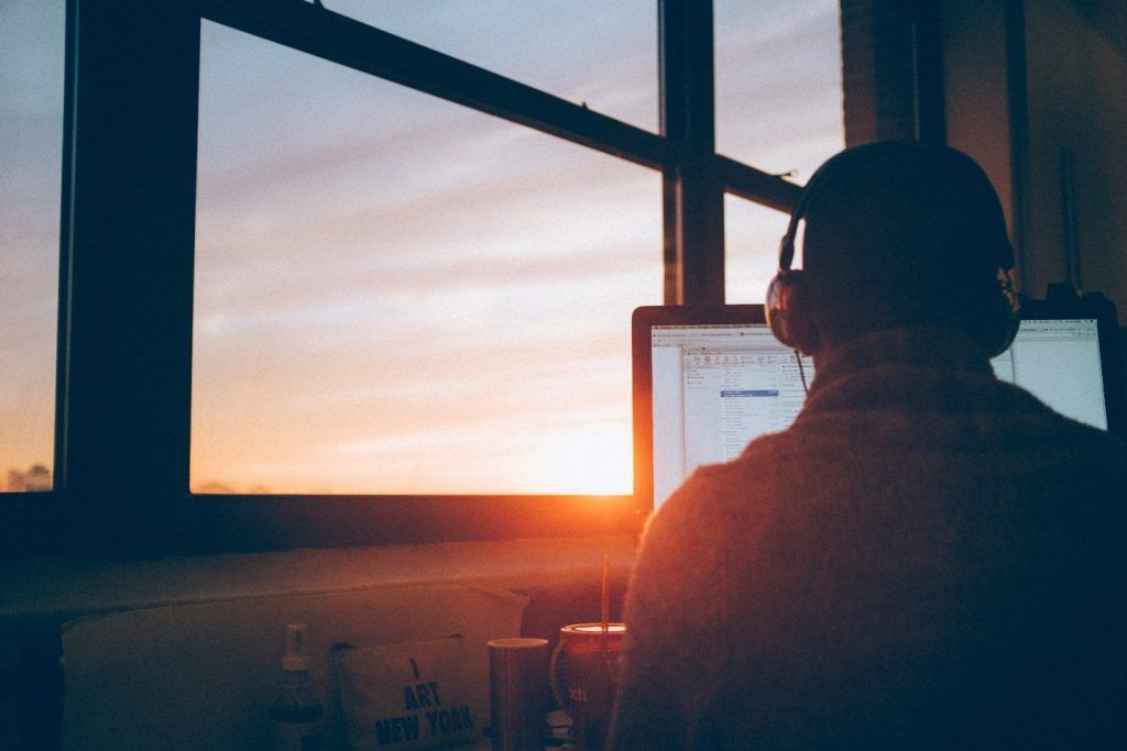 Man looking out of a window with his laptop, duplicate records in sql